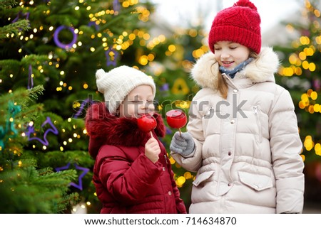 Two adorable little sisters eating red apples covered with sugar icing on traditional Christmas market. Children enjoying sweets, candies and gingerbread on magical Xmas time.