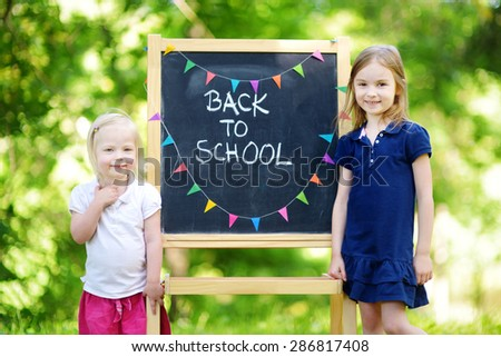 Two adorable little sisters feeling very excited about going back to school - stock photo