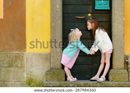 Two adorable little sisters having fun together on warm and sunny summer day in italian town - stock photo