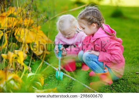 Two adorable little sisters helping in the garden on beautiful autumn day - stock photo