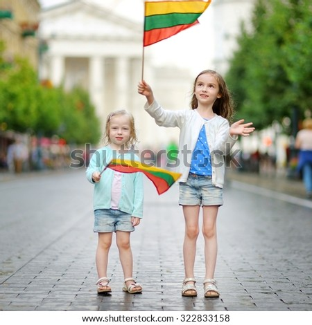Two adorable little sisters holding Lithuanian flags in Vilnius, the capital of Lithuania - stock photo