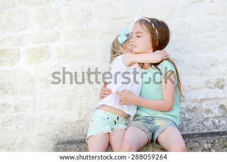Two adorable little sisters laughing and hugging on warm and sunny summer day in italian town - stock photo