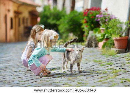 Two adorable little sisters met a cat while walking narrow streets of typical italian town - stock photo