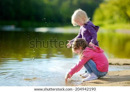 Two adorable little sisters playing by a river in autumn park on a beautiful sunny day - stock photo