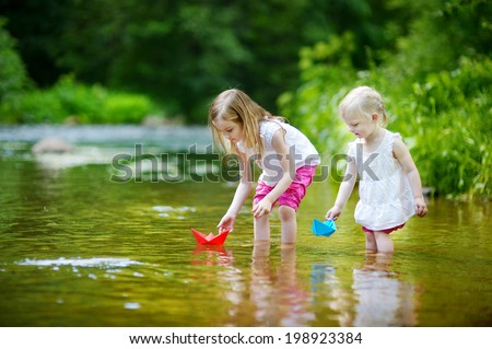 Two adorable little sisters playing with paper boats in a river