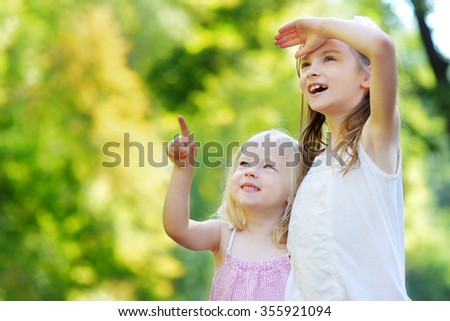 Two adorable little sisters pointing at a plane on the sky on warm and sunny summer day
