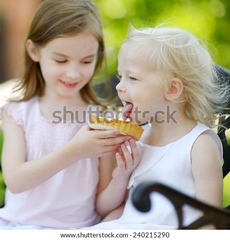 Two adorable little sisters sharing delicious cream tart outdoors on a beautiful and warm summer day - stock photo