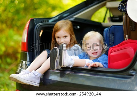 Two adorable little sisters sitting in a car just before leaving for a car vacation with their parents - stock photo