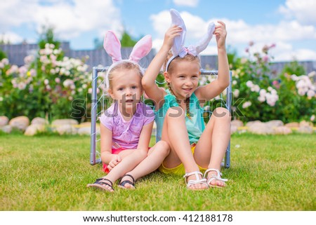 Two adorable little sisters wearing bunny ears on Easter day outdoors - stock photo