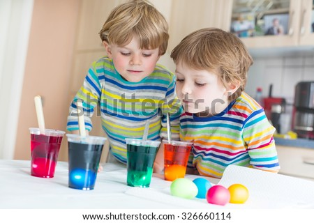 Two adorable little twins boys coloring eggs for Easter holiday in domestic kitchen, indoors. Kids having fun and celebrating feast. - stock photo