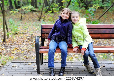 Two adorable preteen girls sitting on a bench  in autumn park