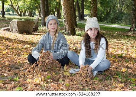 Two adorable school aged girls friends having fun in the autumn