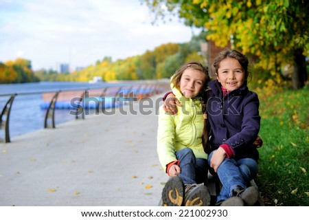 Two adorable school aged tween girls friends having fun in the autumn park, smiling, look into the camera on a beauty autumn day - stock photo