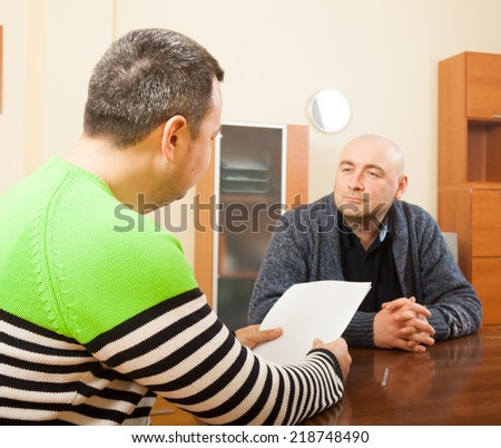 Two adult  friends  talking at home with documents - stock photo