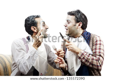 Two adult manwearing old-man clothes and makeup. They both wear napkins on their necks and holding cuttlery, suggesting they are having a meal. But they're too busy fighting. Isolated on white. - stock photo