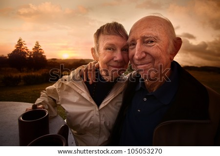 Two adult seniors embracing outside at table - stock photo