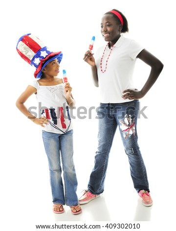 Two African American sisters enjoying tri-colored Popsicles together while wearing their country's colors.  On a white background. - stock photo