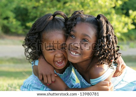 Two african american sisters playing in a park - stock photo