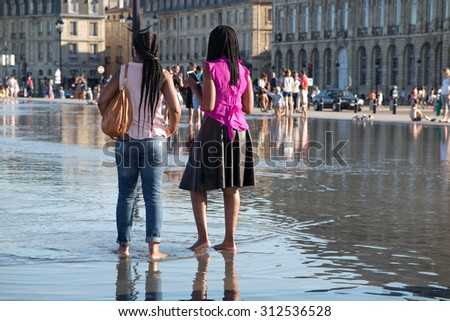 Two african girlfriends standing in the water