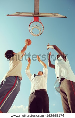 Two Afro-American boy and a man playing basketball against blue sky - stock photo
