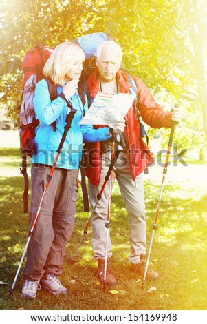 Two aged people with rucksacks looking for way - stock photo