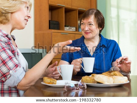 Two aged women sitting at the table with tea and having a chat in home interior - stock photo