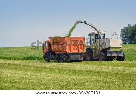 Two agricultural vehicle harvested grass on the field.
