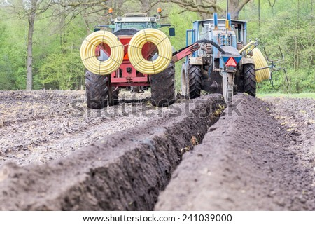 Two agriculture tractors digging drainage pipes in ground - stock photo