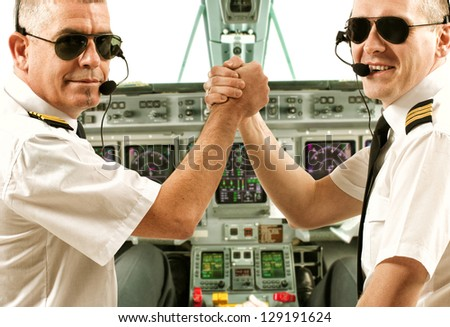 Two airline pilot wearing uniform with epaulettes and headset working in airliner during flight. - stock photo