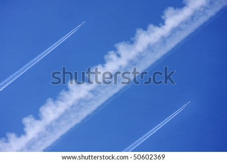 Two airliners with vapour trails - stock photo
