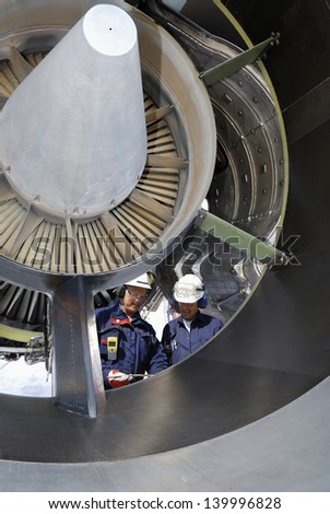 two airplane mechanics standing inside large jumbo jet engine - stock photo
