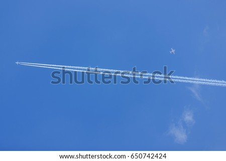 Two airplanes against blue sky.