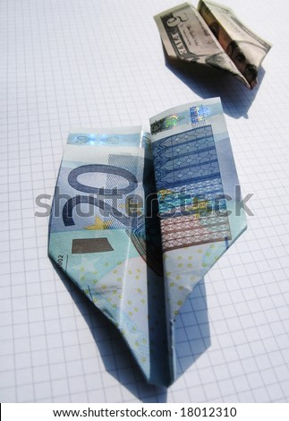 Two airplanes made of euro and dollar notes on squared paper - stock photo