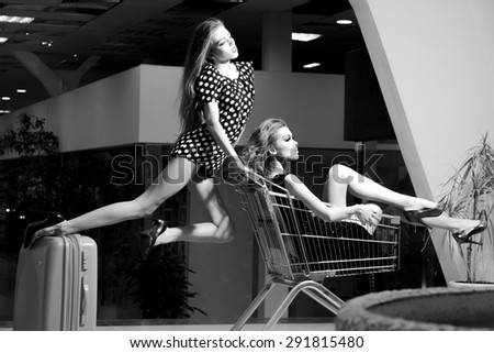 Two alluring fashionable girls in dresses with shopping trolley indoor on shop background black and white, horizontal picture - stock photo