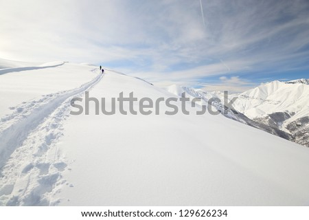 Two alpinist hiking uphill by snowshoeing in powder snow with deep track in the foreground and scenic high mountain view in the background. - stock photo