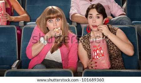 Two amazed women eating popcorn in a theater - stock photo