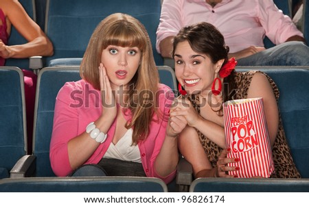 Two amazed women with bag of popcorn watch movie in theater - stock photo