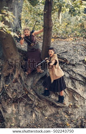 Two Amazons in forest on the background of the tree roots with a swords