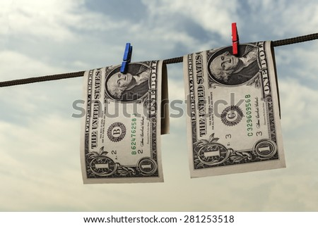 Two american dollars drying on string with sky and trees in the background - stock photo