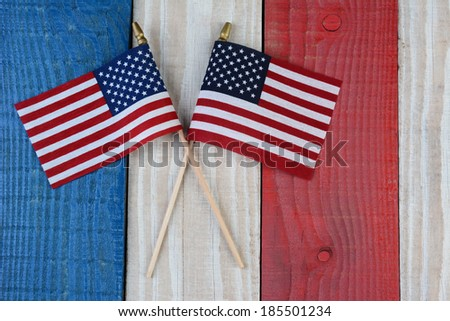 Two American Flags on a red, white and blue painted wood surface. Perfect for Fourth of July or Memorial Day projects. - stock photo