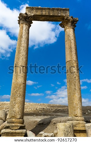 Two ancient Roman columns with capstones support a large flat stone referred to as an abacus. This trio is against a blue sky with a few clouds in Jerash, Jordan. - stock photo