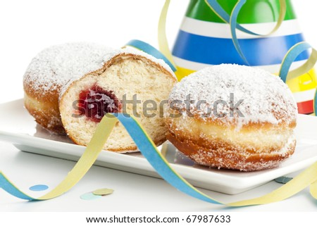two and a half bismarck donuts on a plate surrounded by party decoration