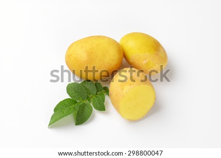 two and half baby potatoes with leaves on white background
