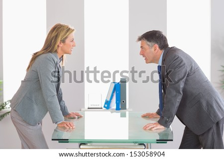 Two angry businesspeople standing arguing on each side of a desk at office - stock photo