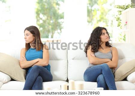 Two angry friends after a quarrel sitting on a couch and looking at the other side - stock photo