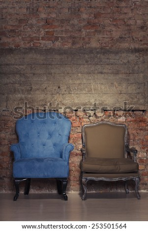 Two antique chairs against a grungy brick wall - stock photo