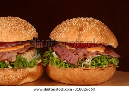 Two appetizing big delicious fresh burgers with green lettuce red tomato cheese cabbage bacon slice meat cutlet and white bread bun with sesame seeds on black background closeup, horizontal picture - stock photo
