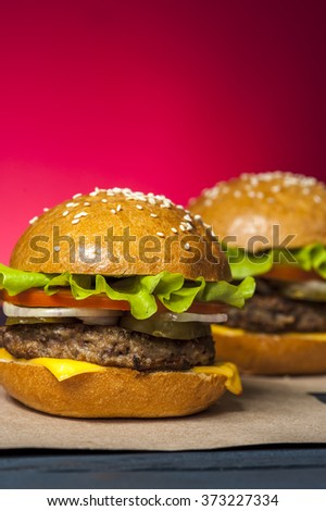 Two appetizing hamburgers with vegetables on wooden table. Fast food, junk food. Focus on first hamburger. Unhealthy food concept.