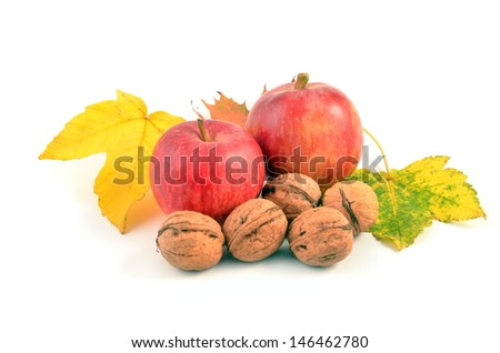 Two apples and nuts with autumn leaves on white background