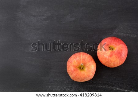 two apples on a chalkboard background with blank space - stock photo